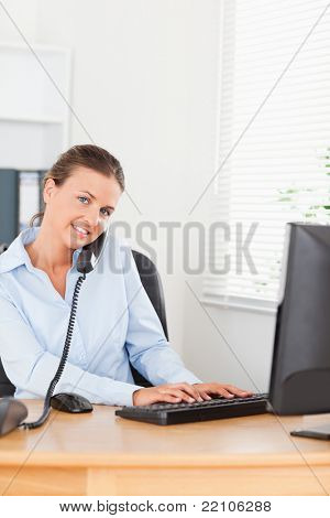 Secretary answering the phone while typing on her keyboard in her office