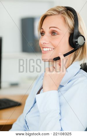 Portrait of a smiling businesswoman with headset looking elsewhere in her office