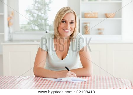 Woman sitting at a table writing a letter looking into camera in the kitchen