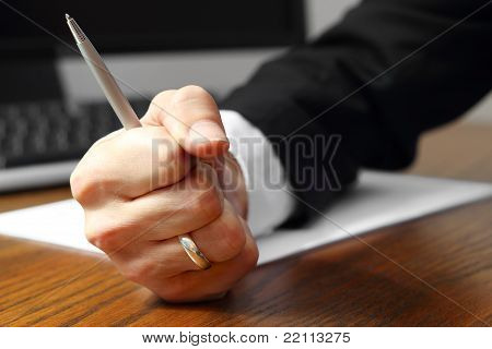 Fist of businessman with pen