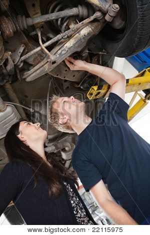 Mechanic showing female customer problems with car