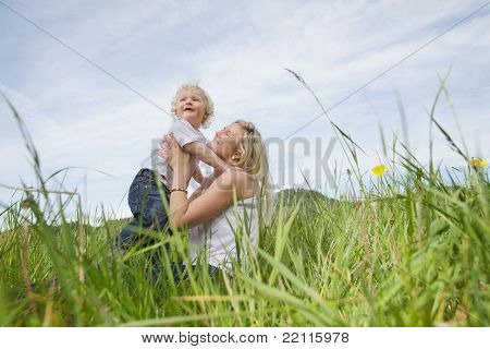 Low angle view of mother sitting on grass and playing with baby boy