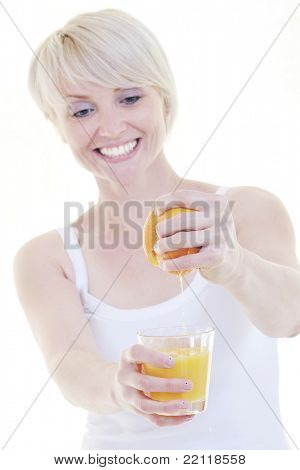 happy Young blonde woman squeeze  orange juice isolated over white background