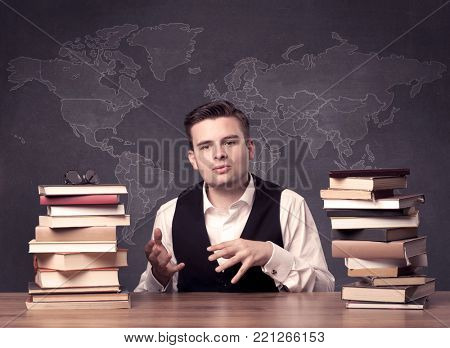 poster of A young ambitious geography teacher in glasses sitting at classroom desk with pile of books in front