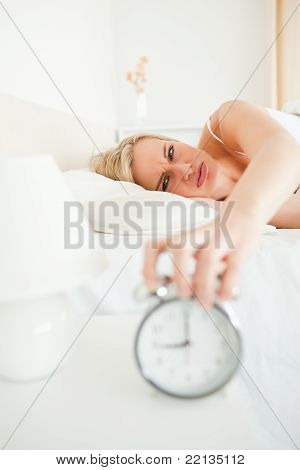 Portrait Of A Tired Woman Switching Off Her Alarm Clock