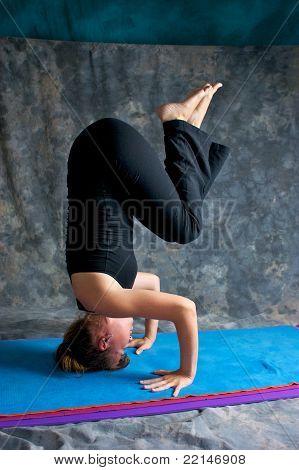 Young Woman Doing Advanced  Yoga Asana Sirsasana Or Headstand