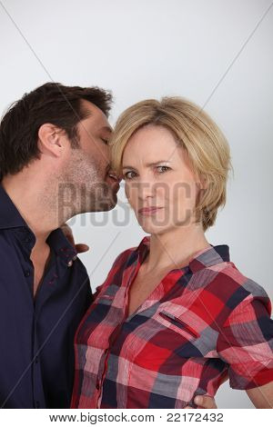 Man whispering a secret to his partner