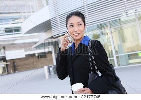 Portrait of pretty asian young  woman with phone at office building