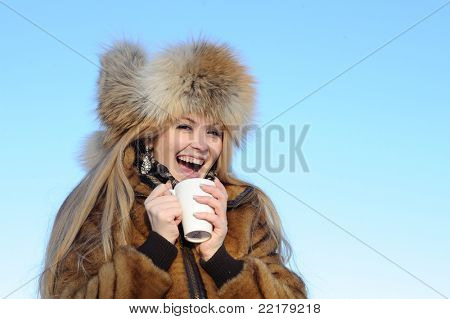 Fun girl in fur coat and hat with cup of tea on the clear blue sky background