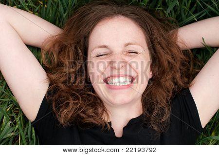 Readhead Woman Laughing Lie On The Grass