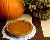 stock photo of pumpkin pie  - A fresh pumpkin pie on display alongside a whole pumpkin and red and green foliage.