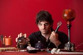 stock photo of sceptre  - Evil man holds sceptre and crystal ball over red background - JPG