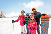 Skiers family together on skiing on ski terrain poster