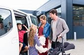 Family checking new car in car dealership with child seat poster
