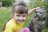 stock photo of girlie  - Girlie smiling near to concrete dog in garden - JPG