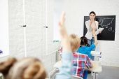 Teacher by blackboard pointing at one of pupils with raised hands at lesson of geography poster