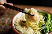 closeup of a young man getting some noodles with his chopsticks from an earthenware bowl with shrimp poster