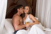 foto of brothel  - Young sexy heterosexual couple celebrating with wine in bed - JPG