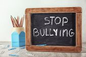 Chalkboard with text Stop bullying on table poster