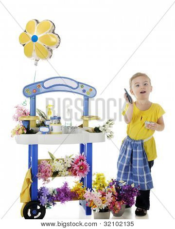 An adorable preschooler by her flower stand happily displaying a fist full of money and a calculator.  The stand's signs are left blank for your text.  White background.