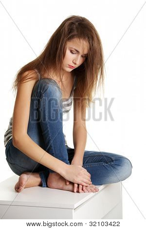 Sad caucasian pretty teen student thinking and touching her head. Sitting on desk. Isolated on white.