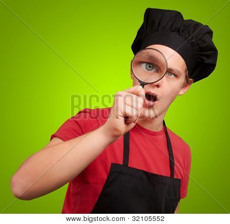 portrait of a young cook man looking through a magnifying glass over a green background