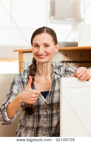 Young woman is assembling a cupboard because she is moving in or out - thumps up