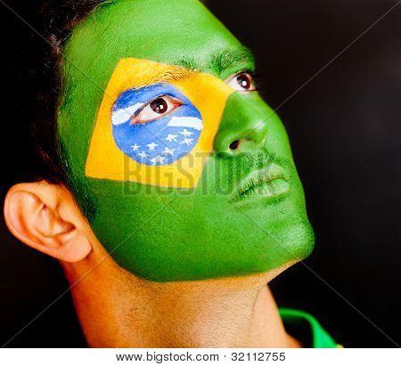 stolz brasilianischen Männchen mit Flagge auf seinem Gesicht isoliert schwarz lackiert
