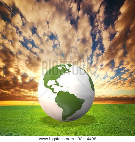 Planet Earth model on green field at sunset. Environement, ecology, clean energy concepts