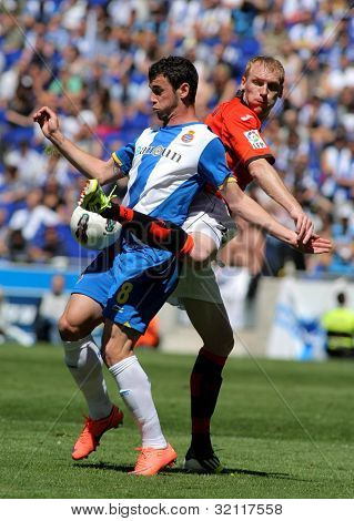 BARCELONA - APRIL 15: Alvaro Vazquez of Espanyol fights with Jeremy Mathieu of Valencia CF during a Spanish League match against at the Estadi Cornella on April 15, 2012 in Barcelona, Spain