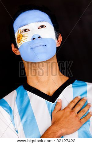 Proud Argentinean man with hand on heart - isolated over a black background