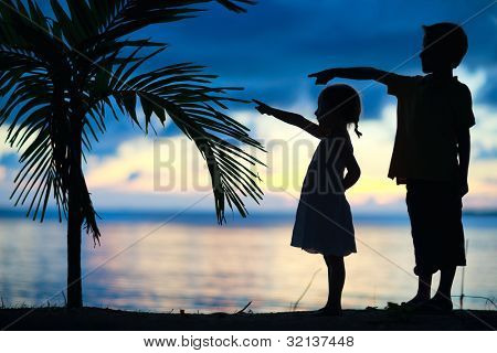 Silhouettes of two little kids at sunset