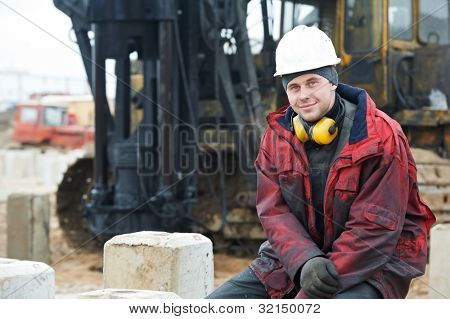Smiling Builder repairman worker in dirty workwear at construction site