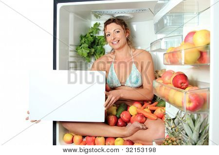 Woman sitting in a fridge in the lotus position surrounded by fruits holding white board