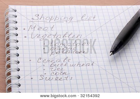 Shoping list and pen on wooden table