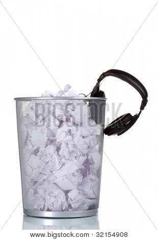 headphones and paper in metal trash bin isolated on white