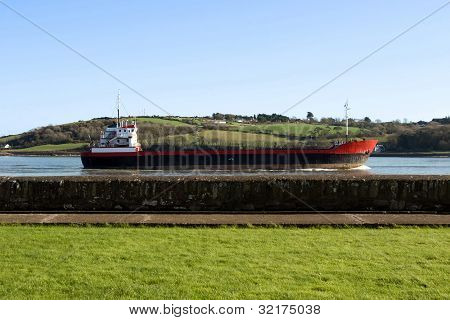 Cargo Ship Sailing Past Sea Wall