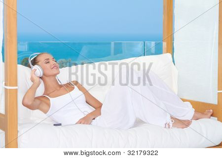 Dreaming woman wearing headphones relaxing on a white sofa listening to music
