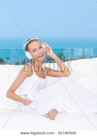 Vivacious laughing woman wearing headphones relaxing on a white sofa listening to music