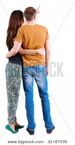 Back view of young couple pointing at wall. guy in the jeans and orange T-shirt and the girl in a fashion pants. looking into the distance. Rear view. Isolated over white background.