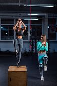 Fit Young Woman Doing Box Jumping At A Crossfit Style On Dark Background With Copy Space. Female Tra poster