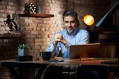 Businessman working at desk in loft office using tablet computer. poster