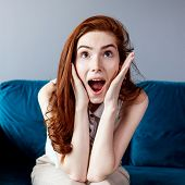 Beautiful Suprised Redhead Woman Sitting On The Blue Couch At Home. poster