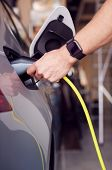 Close Up Of Hand Attaching Power Cable To Environmentally Friendly Zero Emission Electric Car poster