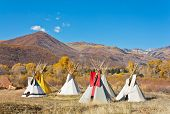 pic of teepee  - A small group of teepees forms a small camp in an autumn mountain meadow - JPG