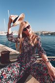 Happy Young Blonde Mediterranean Woman Enjoying Sightseeing At Sea, Holding Hat poster