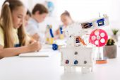 Robot At Desk With Schoolchildren At Background In Stem Class, Copy Space poster