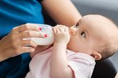 family, babyhood and people concept - close up of mother feeding baby with milk formula from bottle poster