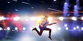 Guitar player jumping with guitar while playing poster
