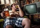 image of beer-belly  - fat man eating hamburger seated on armchair - JPG